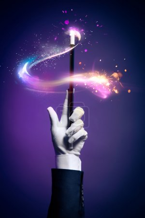 High contrast image of magician hand holds magic w...
