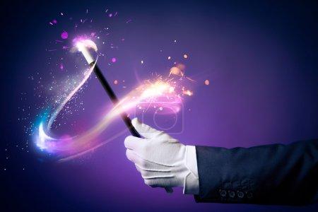 Photo pour Image de contraste élevé de magicien main tient la baguette magique sur fond - image libre de droit