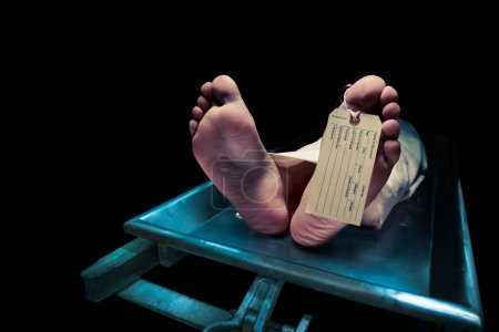 Grungy photo of Feet on a morgue table with toe ta...