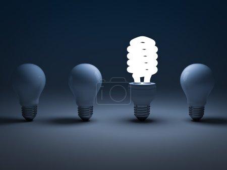 Eco energy saving light bulb , one glowing compact fluorescent lightbulb standing amongst the unlit incandescent bulbs