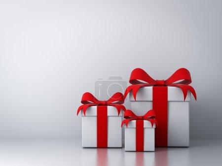 Photo pour Coffrets cadeaux avec ruban rouge arc et fond blanc vide abstrait - image libre de droit