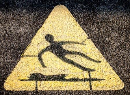 Triangular Hazard Symbol of Man Slipping on Water and Falling