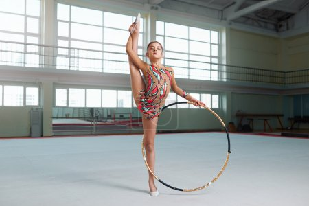 Photo for Little gymnast in a nice suit doing stretching with hoop - Royalty Free Image