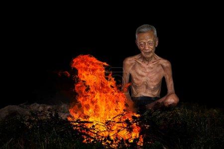 Photo pour Vieil homme assis à côté d'un feu - image libre de droit