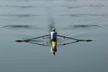One rower in a boat, rowing on the tranquil river
