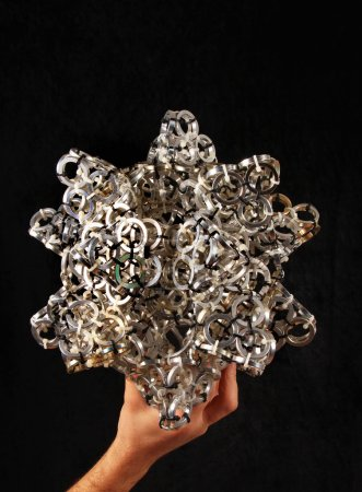 Hand holding artistic composition made of aluminum spacers conca
