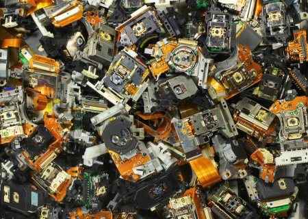 Parts of old optical drives as industrial waste background.