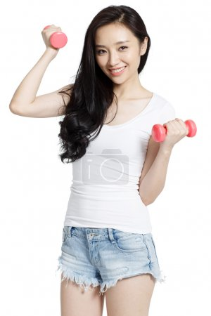 The young woman holding a dumbbell exercise