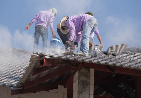 workers installing roof tiles for home building