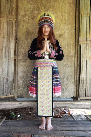 Photo for Traditionally dressed Mhong hill tribe woman pay respect at the wooden cottage - Royalty Free Image