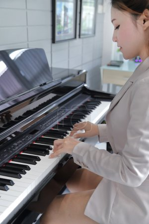 Young beautiful woman playing on piano