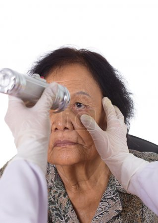 Neurologist testing reflexes of the eye of young w...