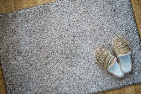 Slippers on the mat, top view with space for text