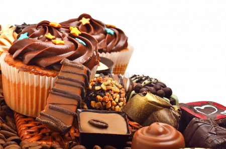 Photo for Chocolate muffins with a heap of chocolate sweets, candies isolated on white background - Royalty Free Image