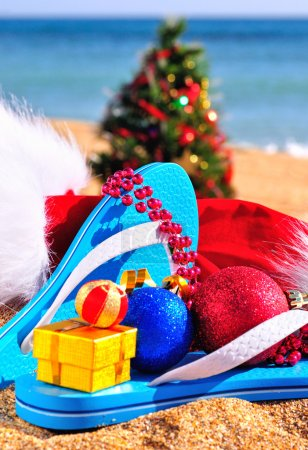 Slippers, christmas hat, gift box and new year tree on the seash