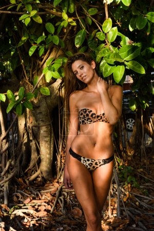 Model posing in front of tropical tree