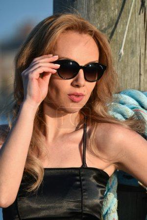 woman wearing black dress and sunglasses