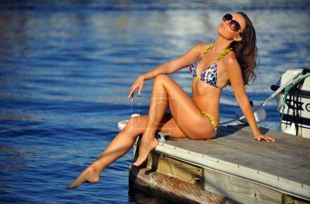 Girl in bikini posing pretty on the pier
