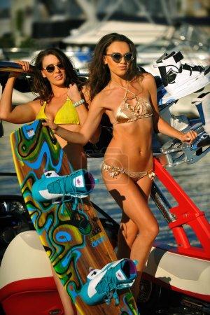 Bikini models posing on the sport speed- boat