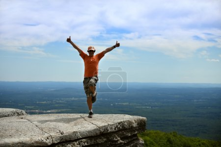 man posing happy on the rock