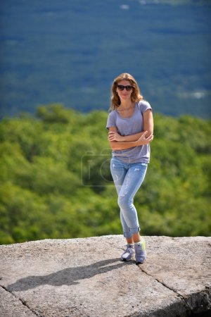 Young woman posing at the edge of rock