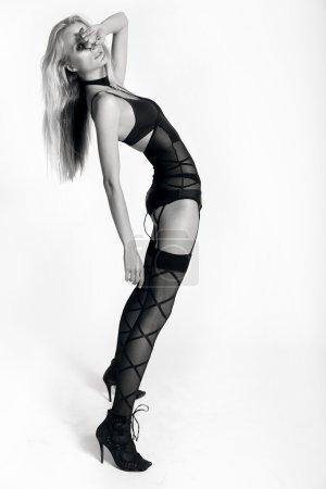 Photo pour Modèle avec les longues jambes sexy archant son dos au fond blanc de studio - image libre de droit
