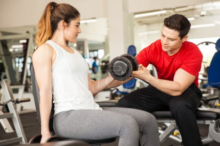 Personal trainer helping a young woman