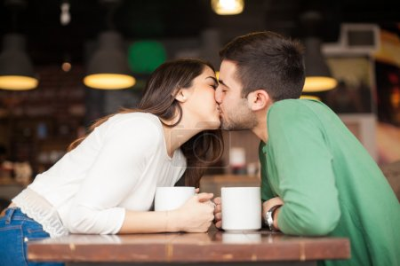 Photo for Profile view of a young couple in love reaching across the table and kissing at a restaurant - Royalty Free Image