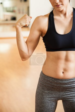 Woman with toned abs flexing her arm