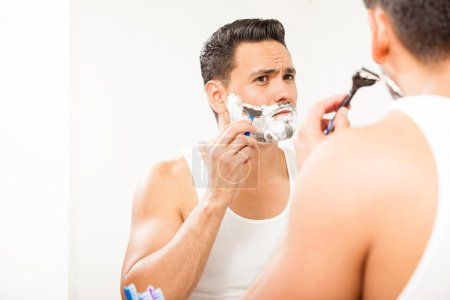 Hispanic man using a razor