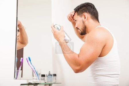 Homme à l'aide de fixatif capillaire en aérosol