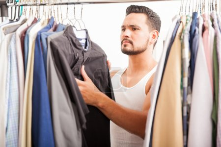 man  trying to find the right shirt