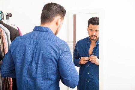 man with a beard putting on a shirt