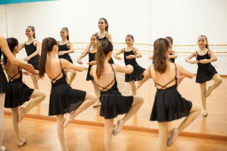 Photo pour Groupe de filles pratiquant quelques mouvements de danse avec leur professeur pendant le cours de danse - image libre de droit