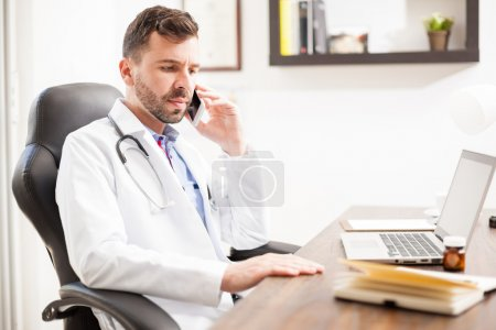pediatrician talking  patient  on the phone