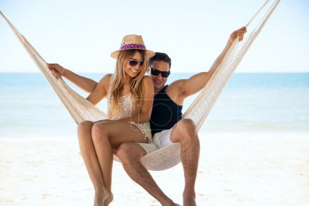 Photo for Portrait of a young couple trying to sit together in a hammock during their vacation on  the beach - Royalty Free Image