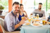 Handsome male eating hamburger with friends