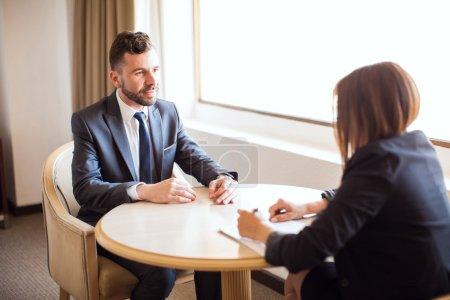 Photo pour Portrait d'un beau jeune homme d'affaires donnant un argumentaire de vente à un client potentiel lors d'une réunion dans un hôtel - image libre de droit