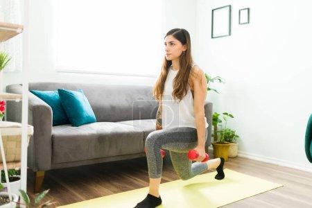 Photo pour Femme latine sportive faisant jambes se jette dans le salon tout en tenant deux haltères. Femme avec un mode de vie sain travaillant à la maison - image libre de droit