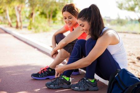 Female friends tying shoes