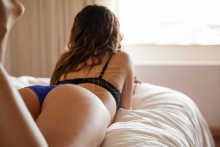 Photo for Rear view of a woman in lingerie and lying on bed while looking at window - Royalty Free Image
