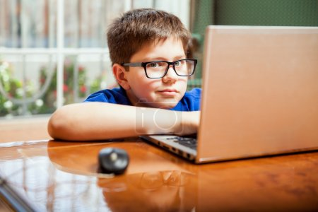 Photo pour Mignon jeune garçon en lunettes surfer sur Internet sur un ordinateur portable à la maison - image libre de droit