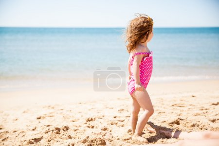 Little girl looking curiously at the ocean