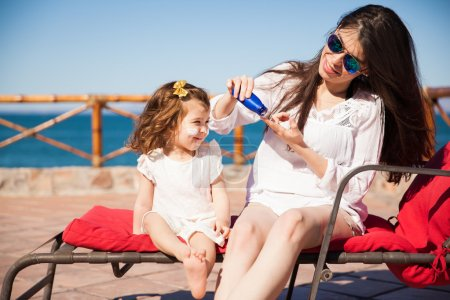 Mom and daughter putting sunblock on