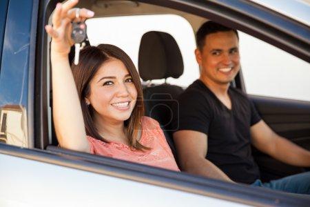 Photo pour Belle jeune femme hispanique assise dans une voiture avec son mari et montrant leurs clés de voiture - image libre de droit