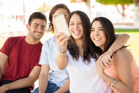 Photo for Group of attractive college students and friends taking a selfie with a smartphone - Royalty Free Image