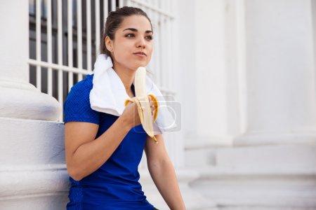 Foto de Bonita chica activa relajarse después de un largo entrenamiento en la ciudad y comer un plátano - Imagen libre de derechos