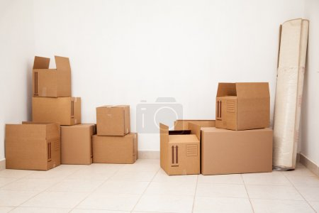 Photo for Empty room full of cardboard boxes for moving to a new home - Royalty Free Image