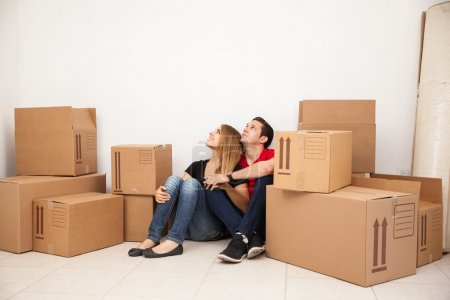 Photo for Cute young couple sitting on the floor of their new home while unpacking things - Royalty Free Image