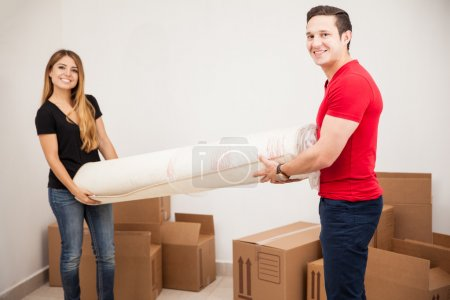 Photo for Portrait of a happy young couple carrying a rolled carpet while moving into their new home - Royalty Free Image